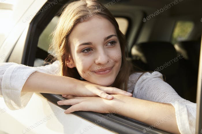 Teenage Girl Looking Out Of Car Window On Family Road Trip