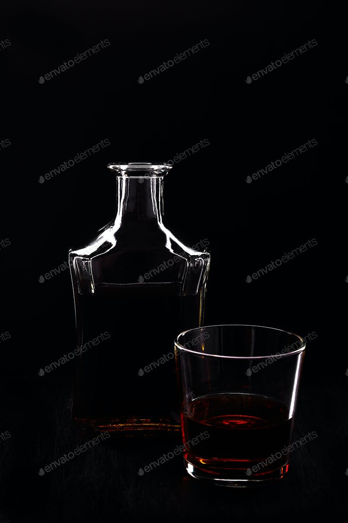 Glass of whiskey with bottle.