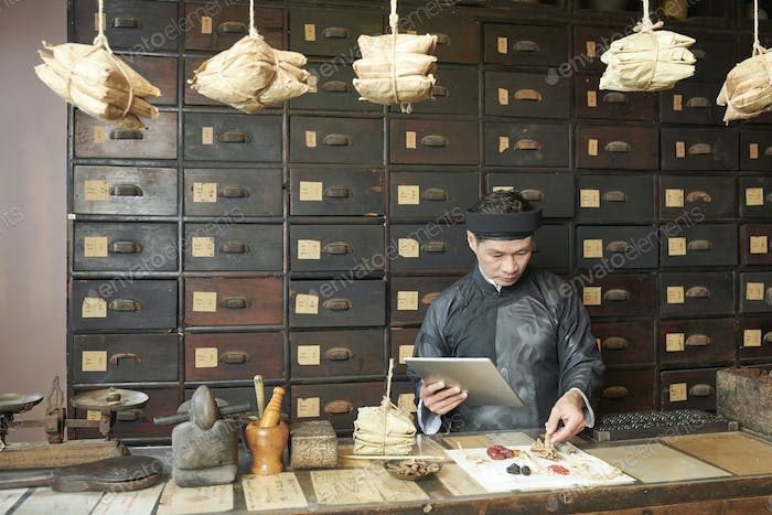 Man selecting dry herbs, mushroom and roots for recipe