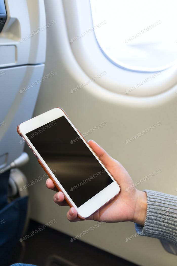 Woman use of smartphone inside airplane