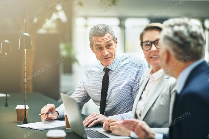Mature work colleagues talking together during an office meeting