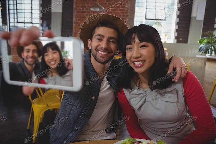 Happy man with woman taking selfie at cafe