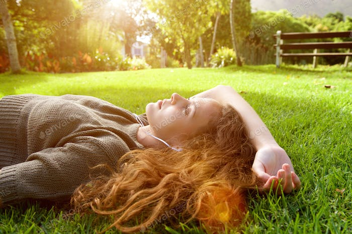 Attractive young woman lying on grass listening to music