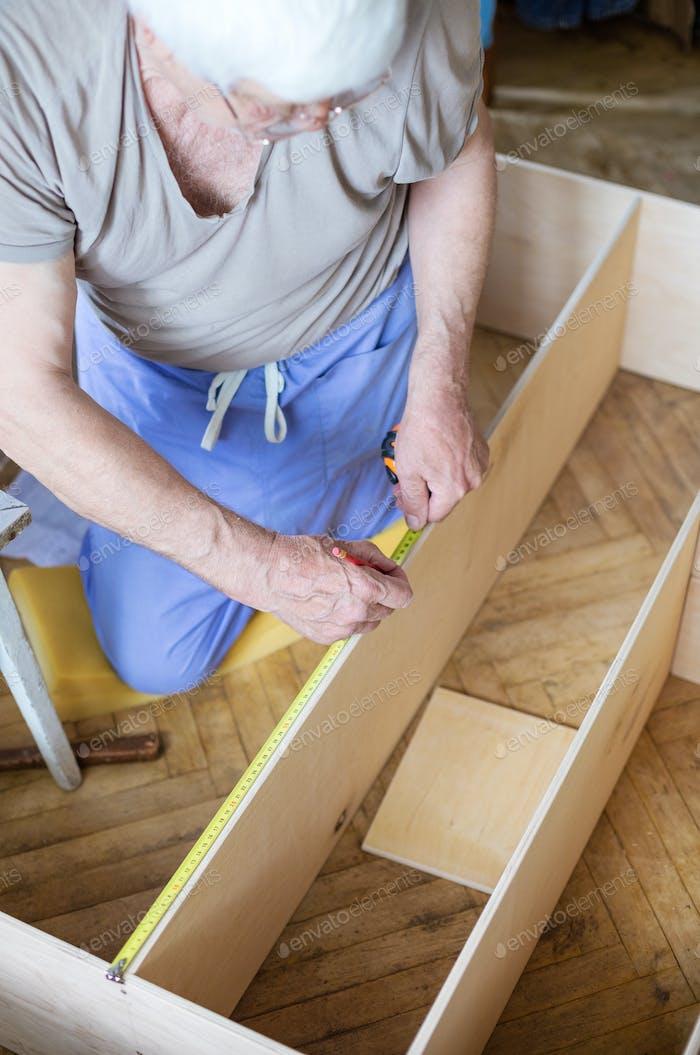 Mature man measuring wooden shelf