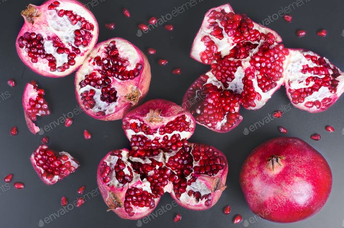 Ripe juice pomegranate fruit on black background - whole and cut, top view. Toned