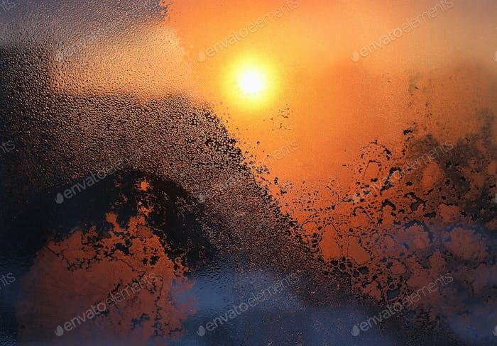 Eismuster, Wassertropfen und Sonnenlicht auf einem Winterfensterglas