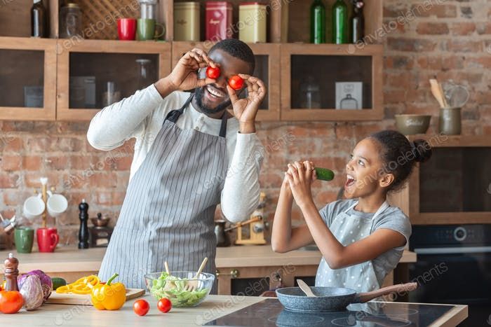 Funny father and daughter having good time at kitchen
