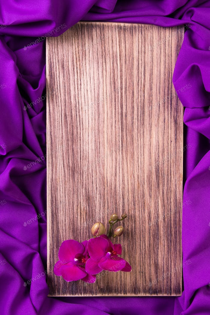 Purple orchid on wooden background.