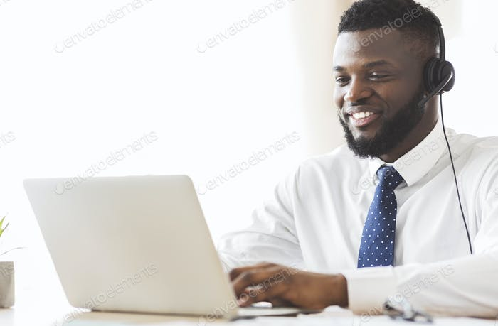 Young business consultant typing email to client on laptop