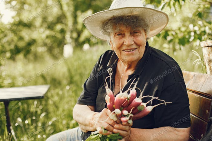 Old woman in a hat holding fresh radishes
