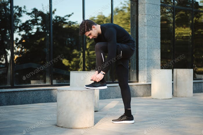 Young attractive confident sporty man tying shoelaces on sneakers during workout on street