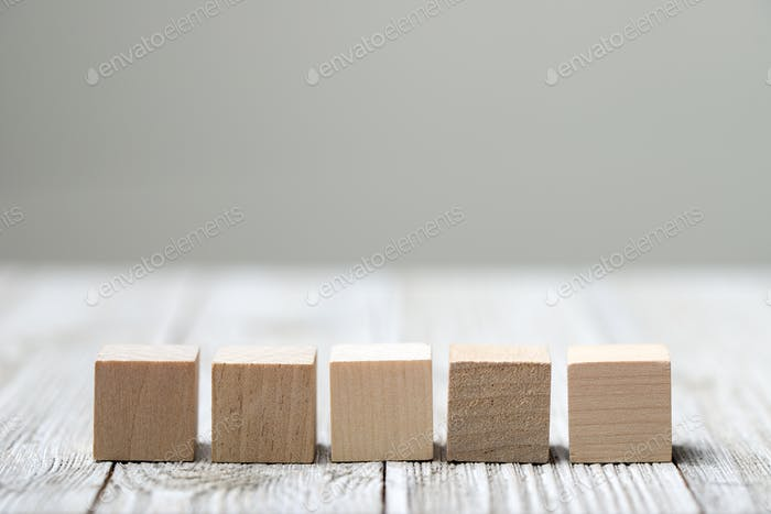 Five wooden toy cubes on grey wooden background