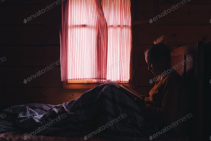 woman reading book in a bed, wooden cottage interior