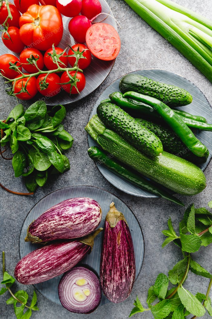 Green, red and purple various fresh vegetables on a table