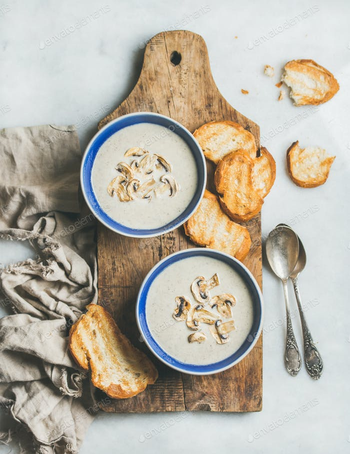 Creamy mushroom soup in bowls with toasted bread, marble background