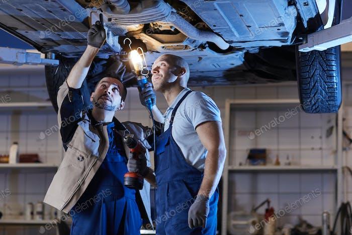 Two Mechanics Inspecting Car on Lift