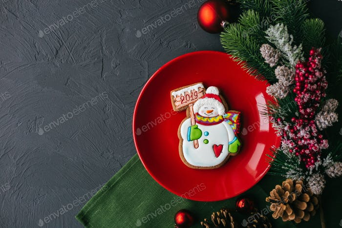 Christmas table with red plate and spruce and bullets. New Year's holiday background