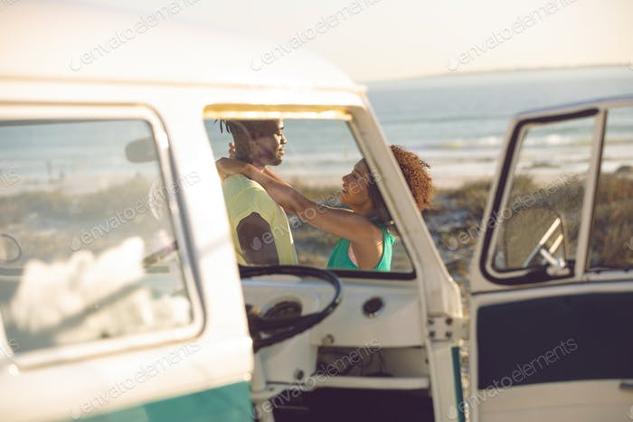 Side view of romantic Caucasian couple embracing each other near camper van at beach