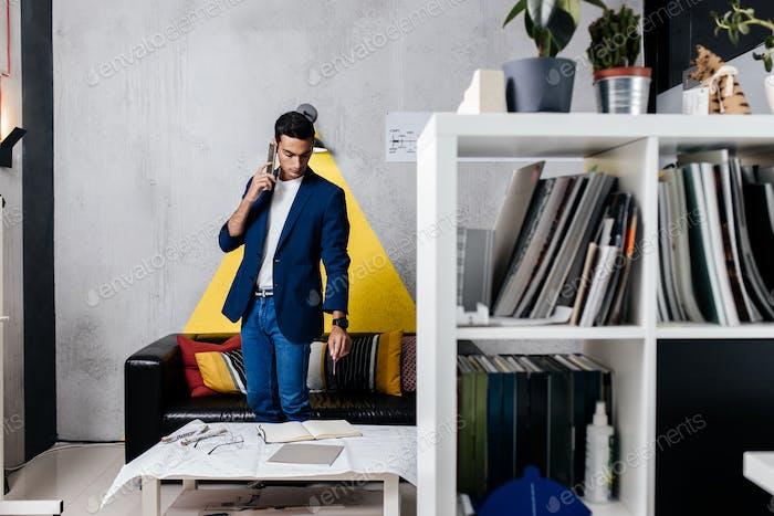 Архитектор разговаривает по телефону в комнате со стильным интерьером с диваном с подушками и