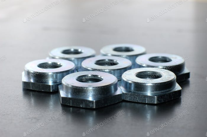 Close-up of several flat metal nuts