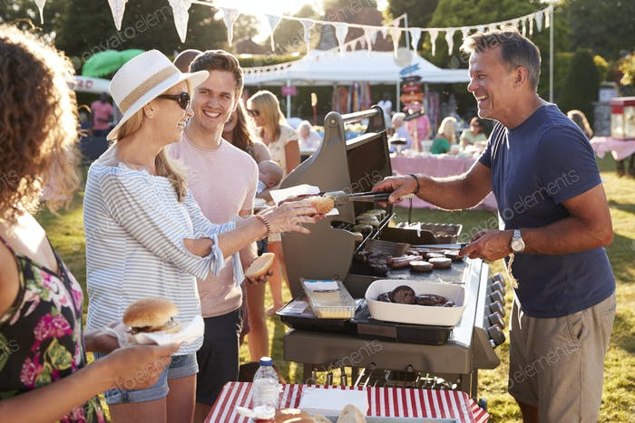 Man Serving On Barbeque Stall At Summer Garden Fete