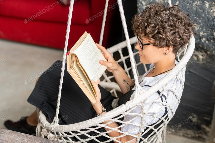Pretty young brunette woman in casualwear reading in hanging armchair