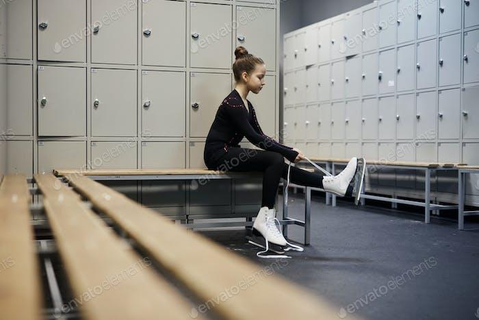 Girl Tying Figure Skates in Dressing Room