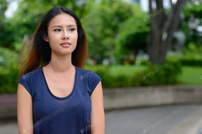 Young beautiful Asian businesswoman thinking in the park