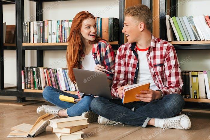 Cheerful teenage couple sitting on a floor at the bookshelf