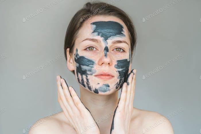 Woman clay face mask peeling natural