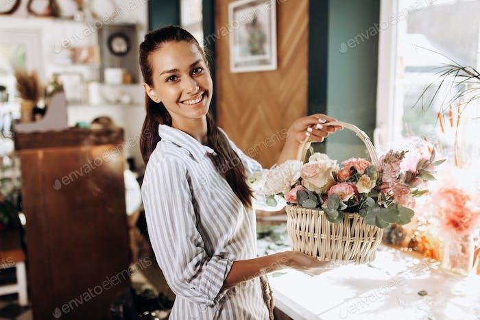 Schöne Brünette Mädchen gekleidet in einem gestreiften Kleid hält Blumenstrauß