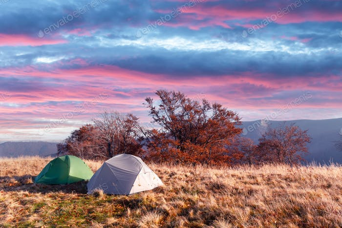 Two tents on amazing meadow in autumn mountains