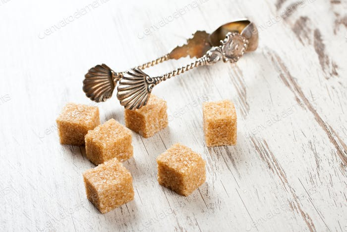 Brown sugar cubes and metal sugat tongs