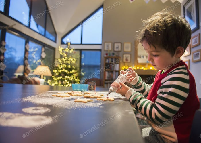 A boy in a red apron decorating Christmas cookies with an icing gun.