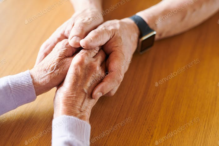 Hands of aged female in those of supportive husband comforting her