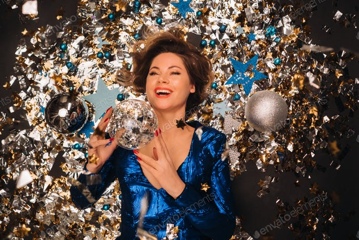 a woman in a blue sequined dress smiles and lies on the floor under a falling multicolored confetti