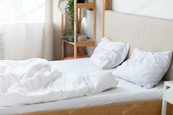 Empty double bed with two pillows and blanket