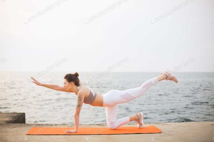 Young woman dreamily practicing yoga by the sea. Pensive girl in