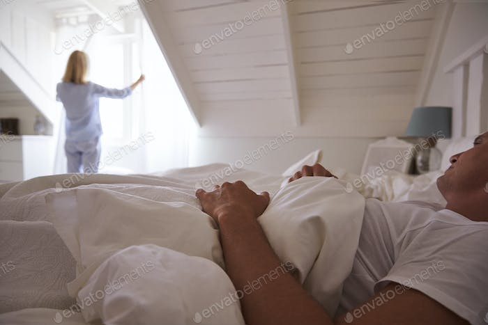 Woman Opens Curtains And Looks Out Of Window As Man Lies In Bed