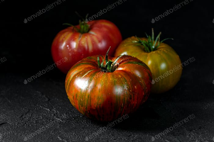 Heirloom tomatoes. Three tomatoes of different colors on a black