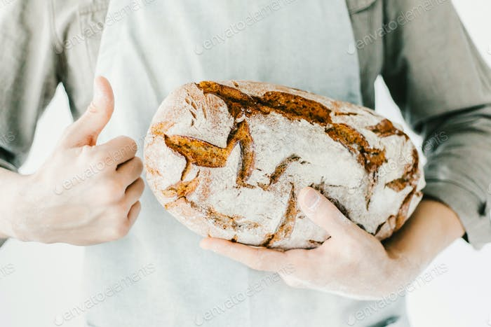 Baker or chef holding fresh made bread