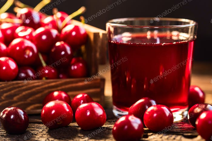 Fresh cherries in a wooden box and cherry juice