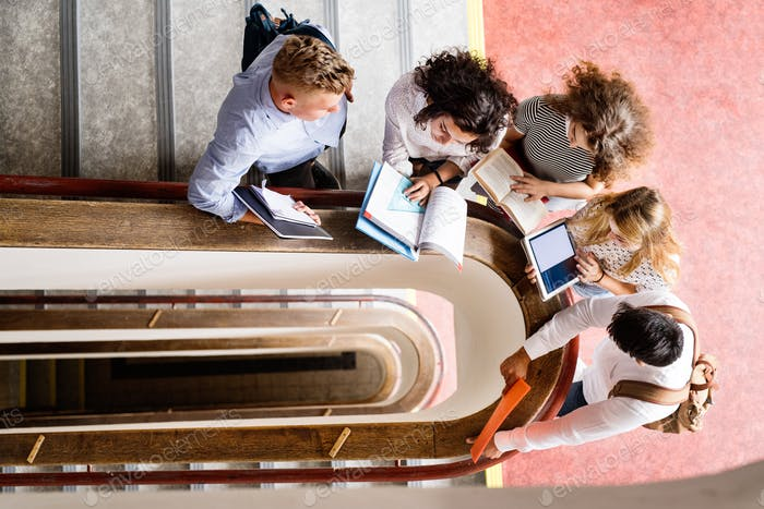 Teenage students on stairs in high school.