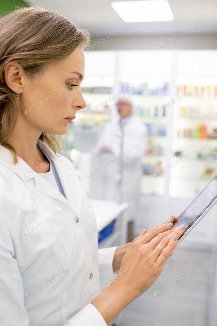 Young blond female pharmacist looking through data on display of digital tablet