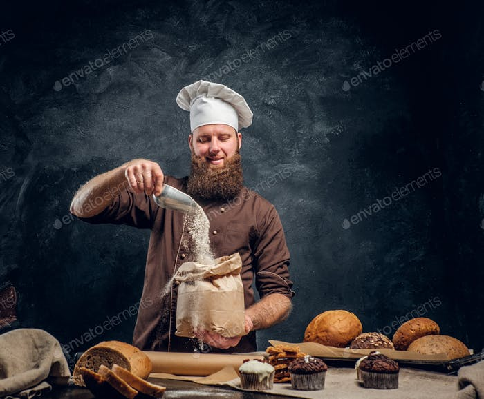 Bearded baker wearing a cook uniform sprinkling some flour in bag
