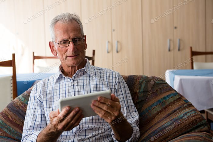 Senior man using tablet computer while sitting on armchair