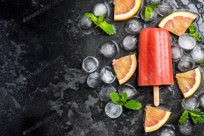 Red orange juice homemade popsicle over ice
