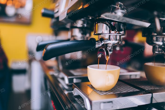 Details of barista preparing fresh espresso on industrial brewing machinery