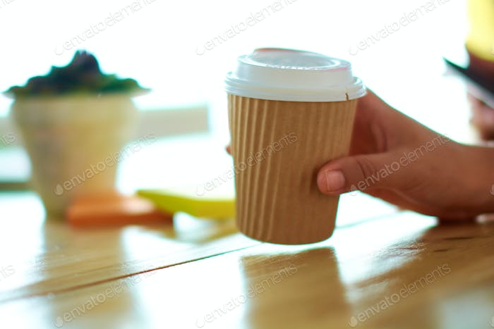 Candid image of a hand holding coffee during an animated brainstorming meeting