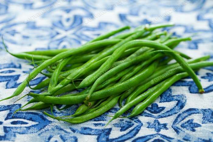 Green beans on blue and white background. Close up.